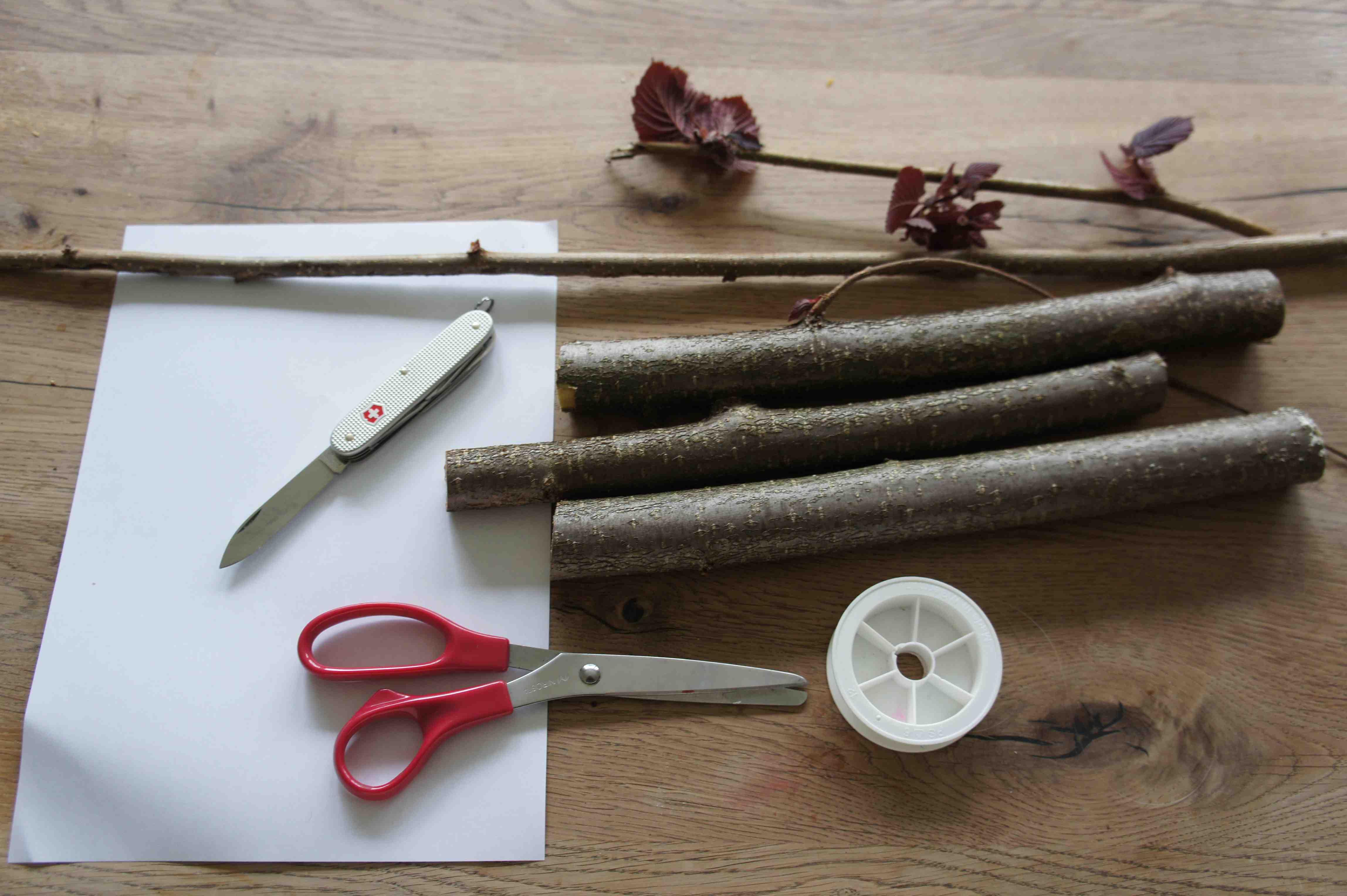 Hier ist alles was Ihr für die Bastelei mit den Kindern braucht: Holz, Papier, Schere,Taschenmesser und eine Nylonschnur (damit das Schiff nicht davon schwimmt). Foto: (c) Kinderoutdoor.de