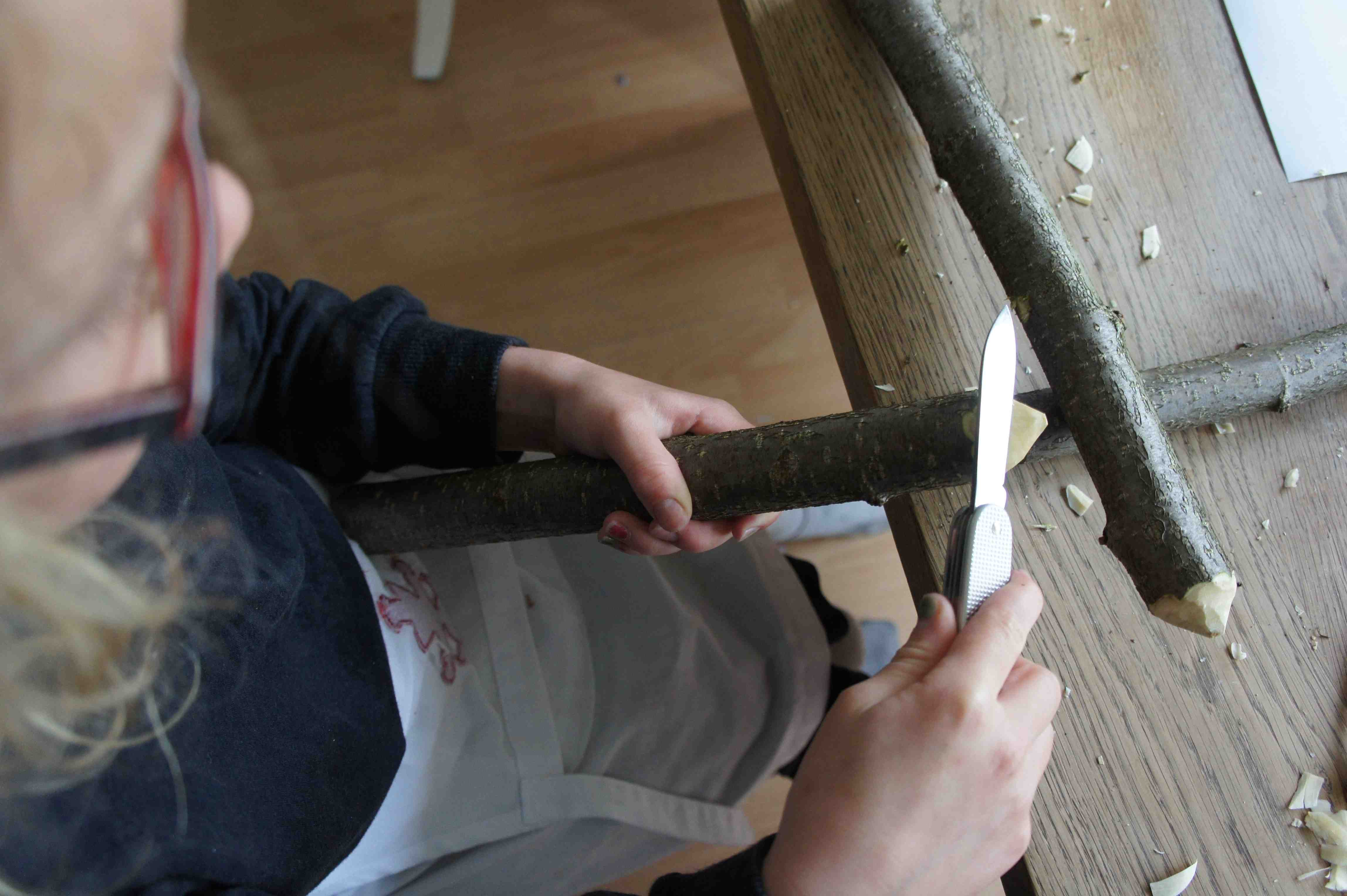 Hier entsteht ein Bootskörper. Mit dem Taschenmesser spitzt Ihr die beiden langen Äste an einem Ende an. Foto: (c) Kinderoutdoor.de