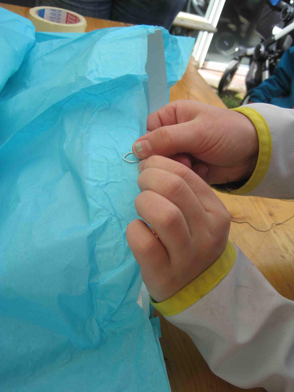 Jetzt klebt Ihr einen Kartonstreifen an der unteren Öffnung vom Ballon innen ein und befestigt daran vier Stück Blumendraht (ca. 10 cm lang).  Foto: (c) Kinderoutdoor.de