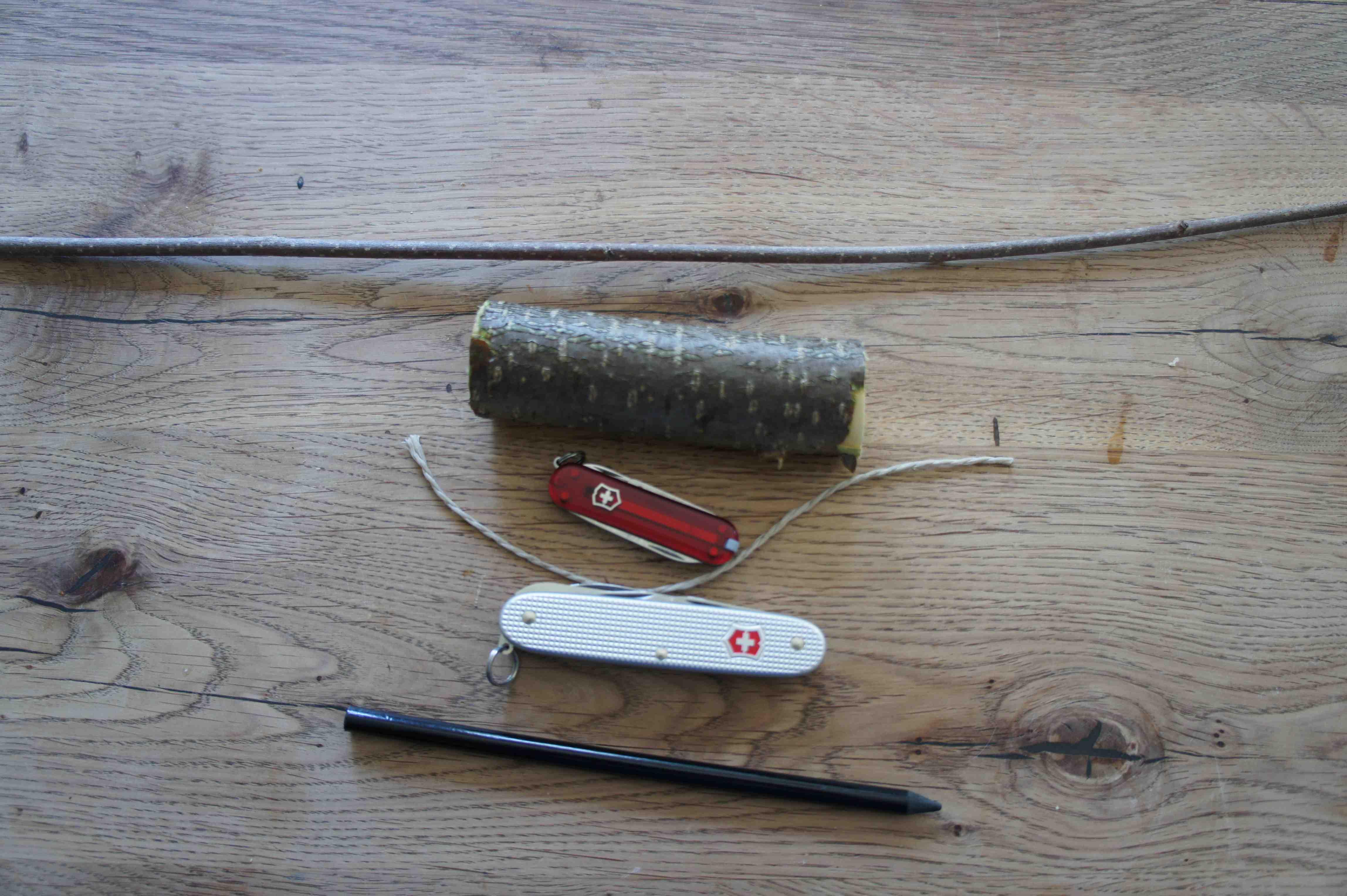 Hier seht Ihr was wir alles für das Schnitzen mit den Kindern brauchen: Ein Stück Haselnuss, ein dünner Zweig, Stift, Schnur und ein Taschenmesser. Foto:(c) Kinderoutdoor.de