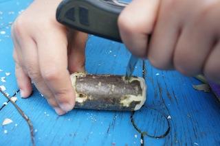 Unsere kleinen Holzschnitzer bohren mit der Ahle (Dorn vom Taschenmesser für Kinder) vier Löcher auf eine Seite des großen Stück Holzes. Foto. (c) Kinderoutdoor.de