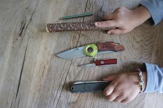 Kinder schnitzen einen Löffel. Hier ist alles was wir dazu brauchen: Holz, Stift und Taschenmesser.  Foto: (c) Kinderoutdoor.de