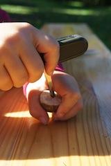 Mit dem Dorn vom Taschenmesser bohren die kleinen Holzschnitzer ein Loch in den Kreisel. Foto: (c) Kinderoutdoor.de