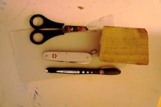 Zum schnitzen vom Marienkäfer braucht Ihr nur eine Schere, ein Stück Papier, einen Holzrest und ein Taschenmesser mit Säge. Foto:(c) Kinderoutoor.de