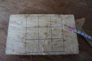 Mit dem Bleistift auf das Spielbrett ein Quadrat zeichnen und es in 3 x 3 quadratische Felder unterteilen.  Foto. (c) Kinderoutdoor.de