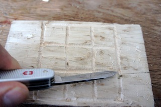 Mit dem Taschenmesser schnitzt Ihr die Linie auf dem Holz nach.  Foto. (c) Kinderoutdoor.de
