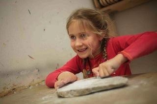 Die Steinzeit selbst erfahren. Ein Mädchen schleift einen Anhänger aus Speckstein. Copyright: Neanderthal Museum/M. Steffen