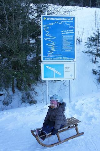 Mit der Rodel am Start der Schlittenbahn: Vier Kilometer und 13 Kehren sowie Kurven geht es die Alpspitz runter. Foto: (c) Kinderoutdoor.de